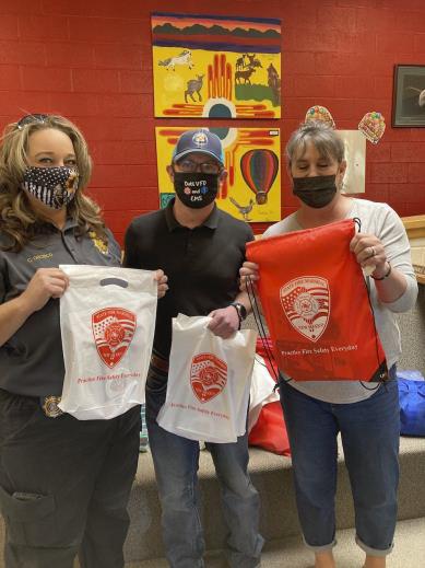 Three people in masks displaying tshirts